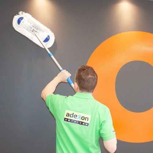 En renholder som vasker en vegg med en mopp